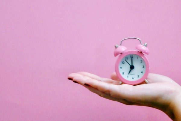 pink clock in plam of hand on pink background